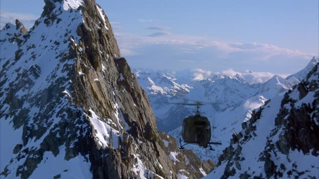 aerial tracking shot of military or army helicopter flying over snow-covered mountains. could be search and rescue. playback, 5.1 stereo surround sound. 6318-039. - military helicopter stock videos & royalty-free footage