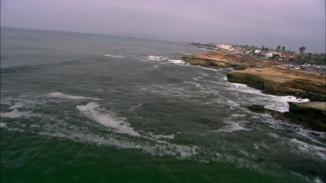 aerial of waves on rocks and cliffs along pacific ocean coastline. ocean beach municipal pier. - san diego stock videos & royalty-free footage