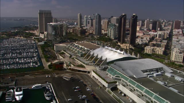aerial of san diego convention center, surrounded by high rise office or apartment buildings in city skyline. hotels. boats in marina. - bay of water stock videos & royalty-free footage