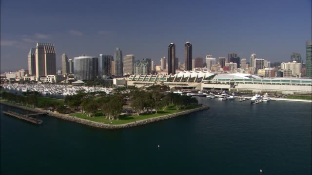 vidéos et rushes de aerial of police cars outside of new children's museum. san diego convention center. boats in marina. high rise office or apartment buildings in city skyline. - san diego