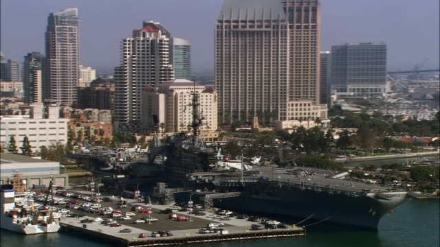 aerial of uss midway, aircraft carrier and navy ship. city skyline in bg. - san diego stock-videos und b-roll-filmmaterial