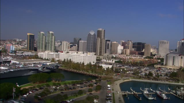 aerial of boats in marina, docks. high rise office or apartment buildings in city skylines. - san diego stock videos & royalty-free footage
