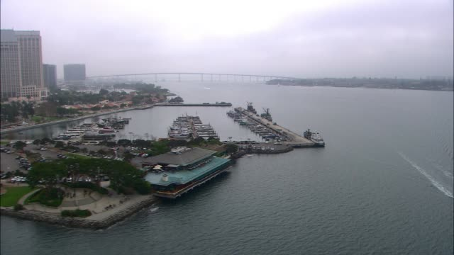 aerial of boats in marina, docks. high rise office or apartment buildings in city skylines. cloudy and overcast. - aircraft carrier stock videos & royalty-free footage