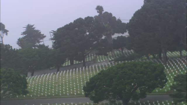 aerial of cemetery or graveyard on hill overlooking pacific ocean. cloudy and overcast. fort rosecrans national cemetery, point loma. - cemetery stock videos & royalty-free footage