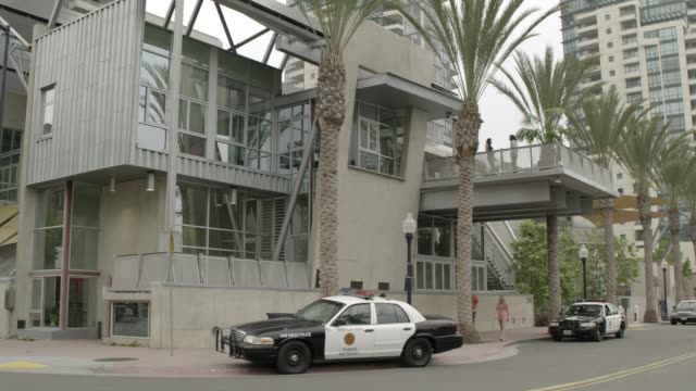 zoom in on police officers and police car outside of two story building. could be police station. - police station stock videos & royalty-free footage