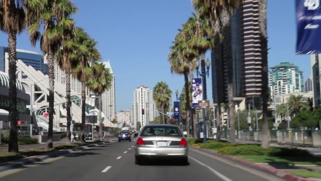 vidéos et rushes de wide angle driving pov stright forward following sedan driving on city streets. stop lights or traffic signals at intersection. - san diego
