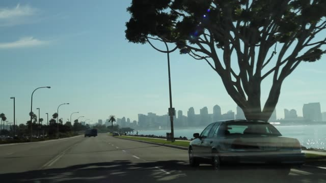 wide angle driving pov forward right of car driving on road along waterfront. san diego city skyline and bay in bg. - san diego stock videos & royalty-free footage