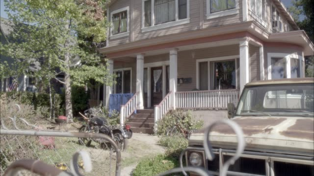 pull back of two story lower class house with porch. pickup truck. chain-link fence. - zweistöckiges wohnhaus stock-videos und b-roll-filmmaterial