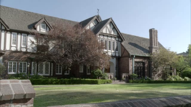 zoom in on two story upper class tudor house or mansion. - zweistöckiges wohnhaus stock-videos und b-roll-filmmaterial