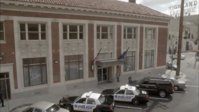 pan down of police station with police cars parked in front. brick building. actually in los angeles. - police station stock videos & royalty-free footage