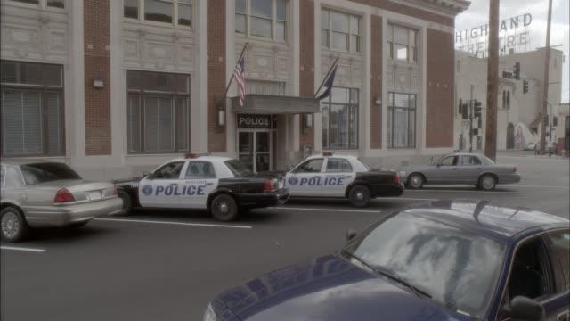 pan up of police station with police cars parked in front. brick building. actually in los angeles. - police station stock videos & royalty-free footage