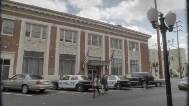 wide angle of police station with police cars parked in front. brick building. actually in los angeles. - police station stock videos & royalty-free footage
