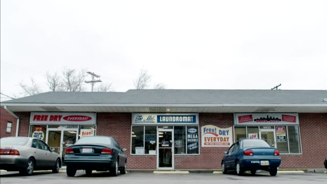 wide angle of laundromat. brick building. - launderette stock videos & royalty-free footage