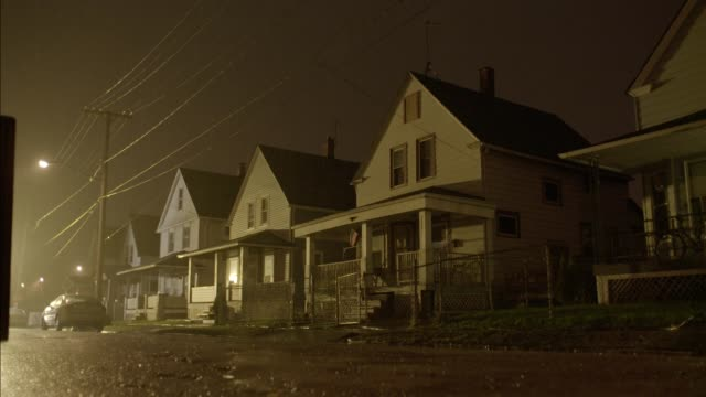 medium angle of two story lower class houses. raining. police car with lights and sirens drives by. - cleveland stock videos and b-roll footage