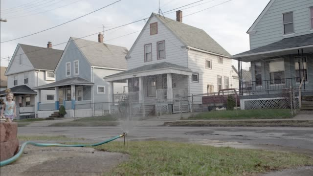 medium angle of two story lower class houses. children running through hose sprinkler on lawn. residential area or neighborhood. - cleveland ohio stock videos & royalty-free footage