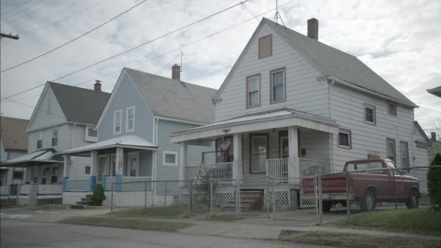 medium angle of row of lower class two story houses. - anno 2002 video stock e b–roll