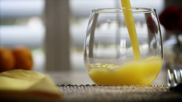 orange juice poured in slow motion hd - drinking glass stock videos & royalty-free footage