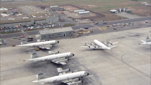 aerial pov to ground of navy airplanes lined up on tarmac. airfield or airstrip. pov from airplane on approach to point mugu naval air station. military base. - us military stock videos & royalty-free footage