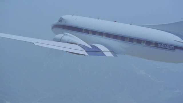 aerial air-to-air tracking shot of all white with  blue stripe twin engine propeller commuter jet or airplane flying over mountains and valley. could be dc-3 airplane. see clear blue sky and rural area with green trees and vegetation below. - propeller video stock e b–roll