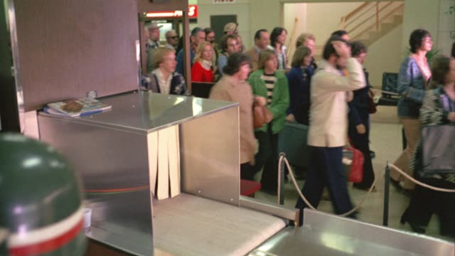 stockvideo's en b-roll-footage met wide angle of people running past armed soldiers through airport security check, x-ray machine. could be emergency or evacuation. crowds. panic. - 1977
