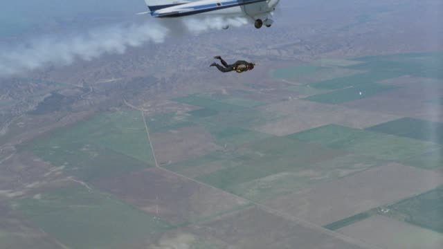 aerial air-to-air tracking shot of man jumping out of airplane single engine cessna 172 with smoke coming from engine. skydiving. mountains and farmland or plains below. could be crop dusting airplane. action. stunts. - skydiving stock videos & royalty-free footage