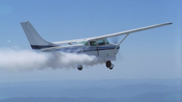 AERIAL TRACKING SHOT OF MAN JUMPING OUT OF AIRPLANE, SINGLE ENGINE CESSNA 172 WITH SMOKE COMING FROM ENGINE. MOUNTAINS VISIBLE BELOW. ACTION. COULD BE AIRPLANE CRASH. STUNTS.