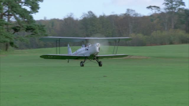 medium angle of single engine biplane or airplane with red and blue british markings taxiing along green field in england. green grass, lawn or field surrounded by trees, woods, or forest. plane takes-off. - 複葉機点の映像素材/bロール