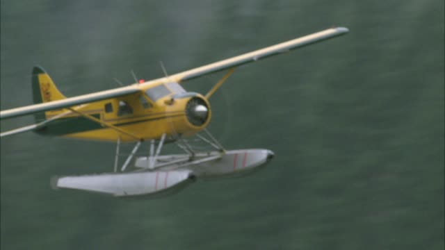 close angle of seaplane flying through trees in woods or forest. mist and fog. pontoon plane. - 水上飛行機点の映像素材/bロール