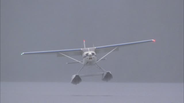 wide angle of blue and white single engine seaplane or airplane landing on water of lake. fog. propeller. - propeller video stock e b–roll
