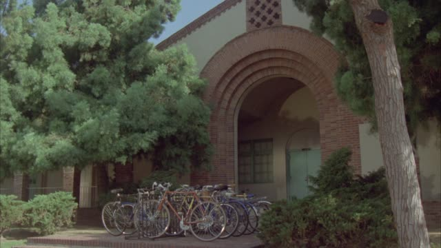 WIDE ANGLE OF ARCHED ENTRANCE TO BRICK BUILDING WITH BIKES LOCKED TO BIKE RANK IN FRONT AND TREES ON BOTH SIDES OF ENTRANCE. COULD BE ELEMENTARY SCHOOL, MIDDLE SCHOOL, OR HIGH SCHOOL OR LIBRARY.