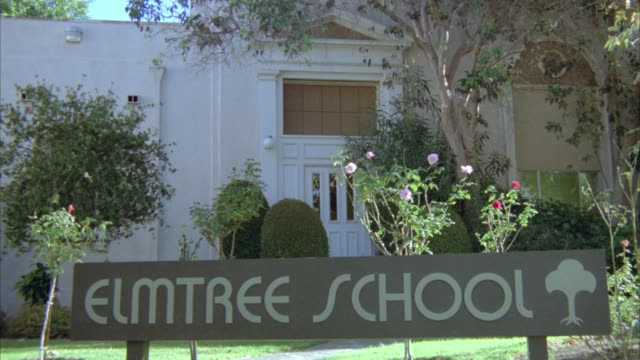 "wide angle of sign reading ""elmtree school"" in front of entrance to two story school with trees, plants in front building. could be elementary school middle school or high school. - junior high stock videos & royalty-free footage"