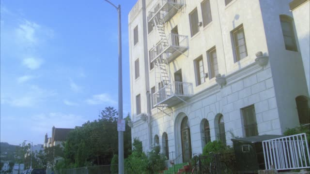 wide angle of four story middle class apartment building with fire escape landings in residential area or neighborhood. - fire escape stock videos & royalty-free footage