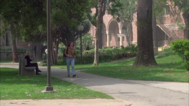 wide angle of students, people walking on sidewalk on college, university or ivy league campus. grass, trees and multi-story brick buildings. usc campus. - ivy league university stock videos and b-roll footage