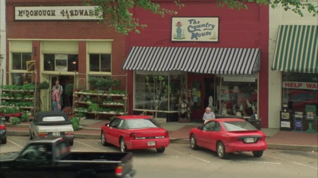 """PAN RIGHT TO LEFT FROM CARS DRIVING PAST SHOPS WITH AWNINGS IN SMALL TOWN, DOWNTOWN TO ENTRANCE OF THREE STORY BRICK BUILDING.  COULD BE PRIVATE SCHOOL, ACADEMY, MIDDLE SCHOOL OR HIGH SCHOOL. SIGN ABOVE ENTRANCE READS """"WELCOME BACK RAWLEY STUDENTS."""" MAIN"""