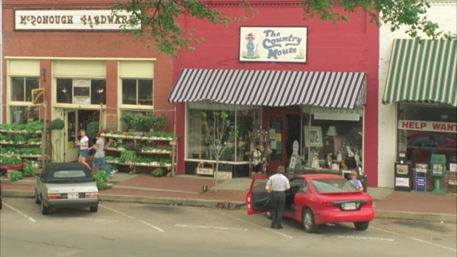 PAN RIGHT TO LEFT OF CARS DRIVING PAST SHOPS WITH AWNINGS IN SMALL TOWN, DOWNTOWN. MAIN STREET.