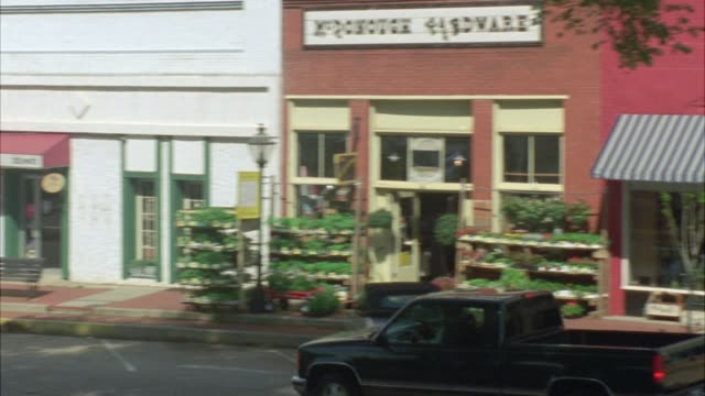 """vídeos y material grabado en eventos de stock de pan right to left from cars driving past shops with awnings in small town, downtown to entrance of three story brick building.  could be private school, academy, middle school or high school. sign above entrance reads """"welcome back rawley students."""" main - street name sign"""