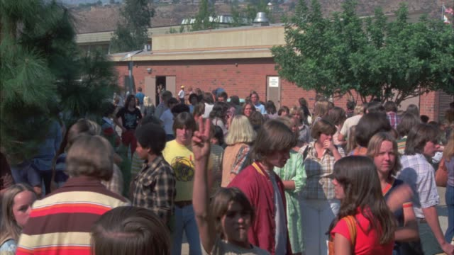 stockvideo's en b-roll-footage met wide angle of students, teenagers, walking around high school campus    crowds of students mill around     usual change of classes type of activity     one student to and by camera several times     could be principal 1970's style and attire  camera pans - 1977