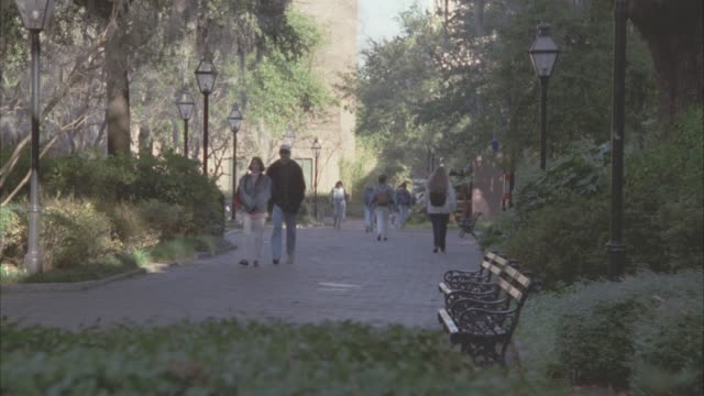 wide angle of people, students wearing backpacks, walking and riding bikes down brick path with trees and multi-story brick buildings on both sides. could be college, university or ivy league campus. could be park. - ivy league university stock videos and b-roll footage