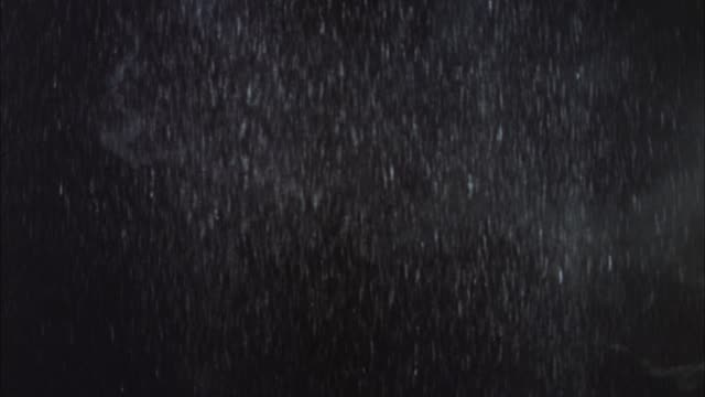 wide angle of rain and lightning flashes against the sky. houses visible when lightening flashes. - lightning stock videos & royalty-free footage