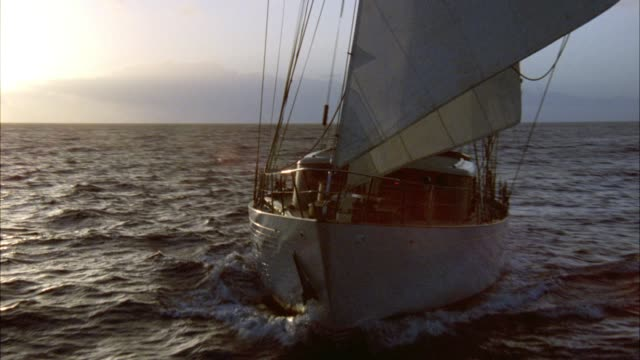 stockvideo's en b-roll-footage met wide angle of large two-mast, white sailboat with american flag hanging off back of boat sailing on ocean during sunset. sun setting behind white clouds on horizon. rippling waves in water. cliffs and high rise office buildings on island or coastline in b - pacifische eilanden