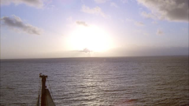 wide angle of large two-mast, white sailboat with american flag hanging off back of boat sailing on ocean during sunset. sun setting behind white clouds on horizon. rippling waves in water. sunlight reflecting off water. - pacific islands stock videos & royalty-free footage