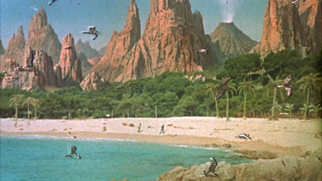 stockvideo's en b-roll-footage met wide angle of island volcano beaches mountains cliff palm trees people walking along beach from a distance rocks - 1961