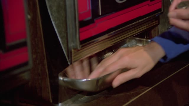 close angle of women's hands grabbing  coins as they fall out of slot machine. casinos. - las vegas stock-videos und b-roll-filmmaterial