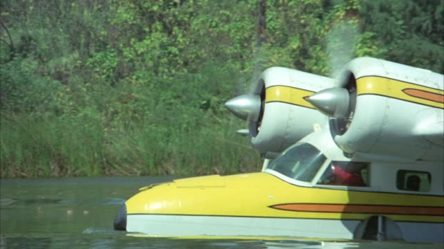 medium angle of seaplane floating in tropical lagoon or lake water. plane stop at a dock and two men secure the boat. see palm trees in background. - 水上飛行機点の映像素材/bロール