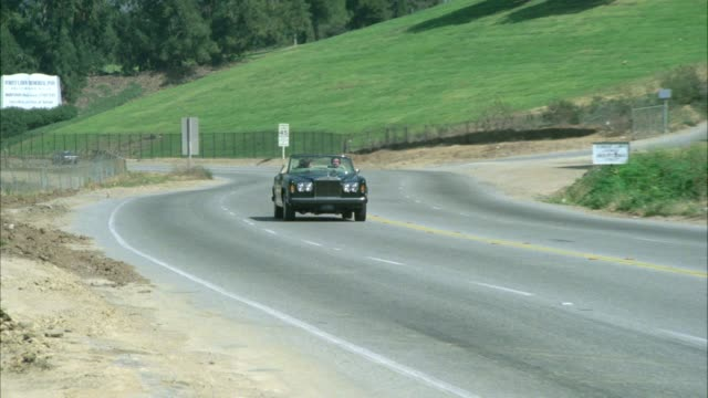 rolls royce convertible with top down driveby l-r with two people / principals / on forest lawn drive - rolls royce videos stock videos & royalty-free footage