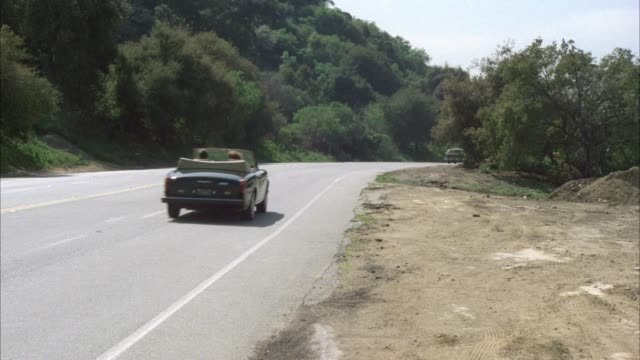 wide angle of cars, rolls royce driving on four lane road, forest lawn drive. hillside covered with plants, trees on left side of road. - rolls royce videos stock videos & royalty-free footage