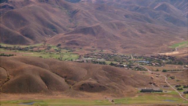 aerial over small town in valley surrounded by barren hills. countryside. - 1977 bildbanksvideor och videomaterial från bakom kulisserna