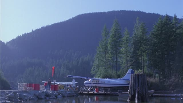WIDE ANGLE OF PLANE SITTING ON DOCK. BOAT VISIBLE IN WATER. PEOPLE STAND ON DOCK AS PONTOON PLANE FLIES OVERHEAD. MOUNTAINS AND FORESTS IN BG. STONE PILINGS OR JETTY. PINE TREES. COULD BE OUTPOST.
