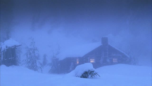 wide angle log cabin in heavy snow. could be mountain. smoke comes from chimney. could be blizzard. - 小屋点の映像素材/bロール