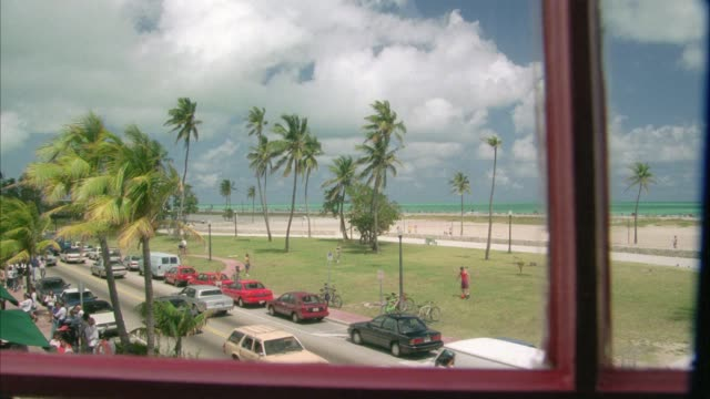 wide angle of beach and ocean from window of multi-story building. could be miami beach or north beach. cars driving on street and people playing in park in fg. palm trees. tropical location. florida. - 1993 stock videos & royalty-free footage